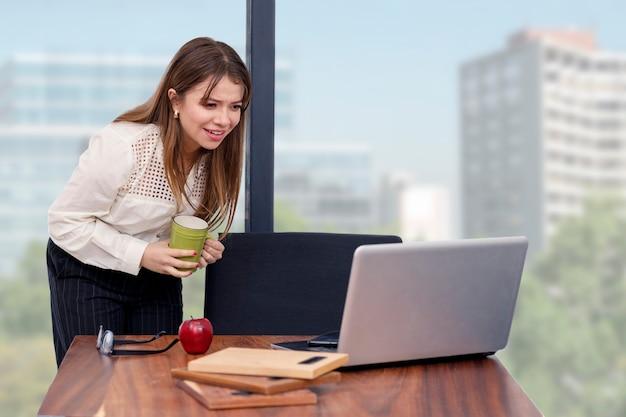 Junge architektin mit einem kaffee in der hand, die von zu hause aus mit blick auf ihren computer arbeitet