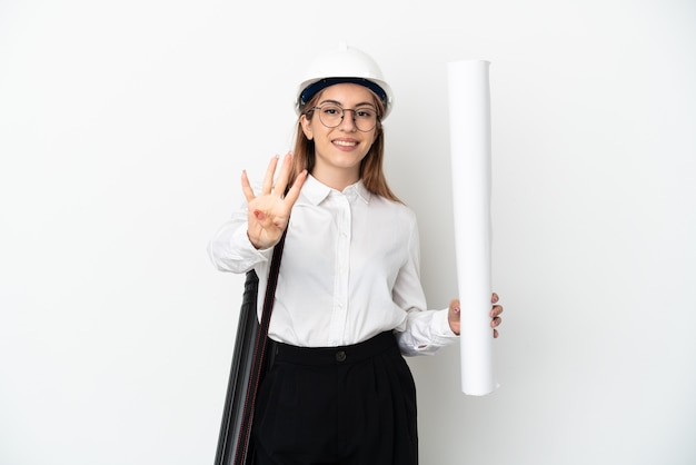 Junge architektin mit helm und hält blaupausen lokalisiert auf weißer wand glücklich und zählt vier mit den fingern