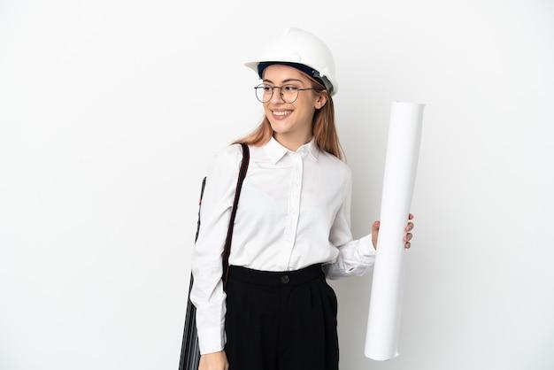 Junge architektin mit helm und halten blaupausen lokalisiert auf weißer wand, die zur seite schaut und lächelt