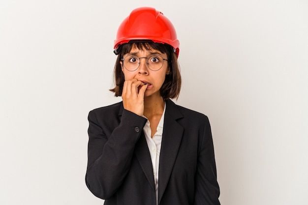 Junge architektin mit rotem helm auf weißem hintergrund beißende fingernägel, nervös und sehr ängstlich.