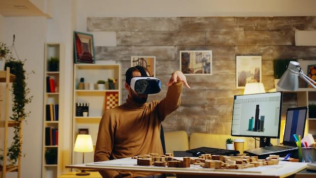 Junge architektin mit virtual-reality-brille, die gebäude im home office modelliert.