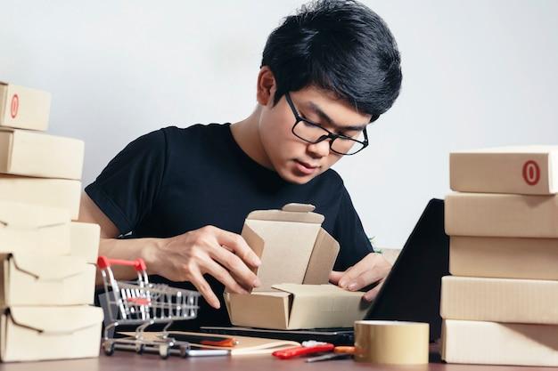 Junge asiaten packen für die lieferung an die kunden