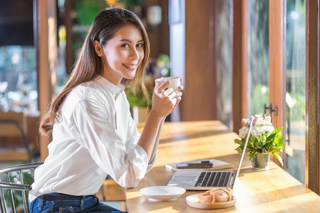 Junge asiatin des porträts, die einen tasse kaffee hält und trinkt und mit technologielaptop an einer kaffeestube arbeitet