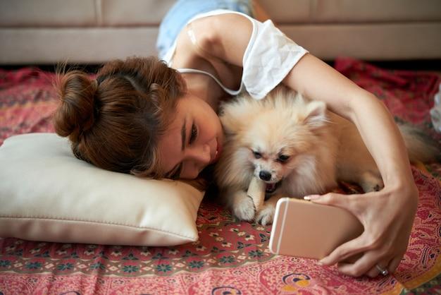 Junge asiatin, die auf boden mit kleinem schoßhund liegt und selfies mit smartphone nimmt