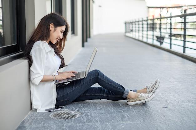 Junge asiatin, die auf der straße sitzt und mit ihrem laptop bei der unterhaltung am handy arbeitet