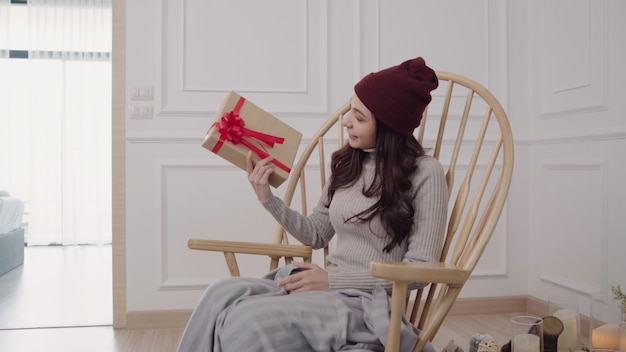 Junge asiatin, die auf einem stuhl zu hause eingewickelt in der grauen decke in ihrem wohnzimmer sitzt.