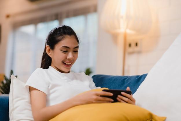 Junge asiatin, die den smartphone überprüft social media verwendet, das glücklichem lächeln glaubt