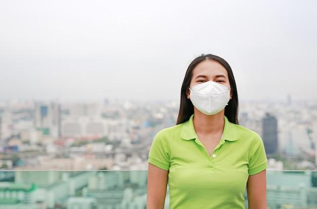Junge asiatin, die eine schutzmaske gegen luftverschmutzung in bangkok-stadt trägt.