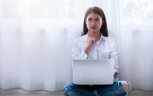 Junge asiatin, die ernste entscheidung beim sitzen auf boden und bei der anwendung des laptops trifft.