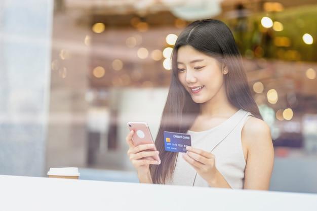 Junge asiatin, die kreditkarte mit handy in der kaffeestube verwendet