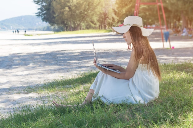 Junge asiatin, die laptop im kleid sitzt auf dem strand, mädchen-freiberufler arbeitet an meer verwendet