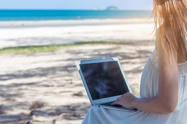 Junge asiatin, die laptop im kleid sitzt auf dem strand, mädchenfreiberuflerfunktion verwendet