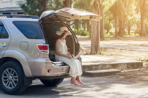 Junge asiatin, die laptop im kleid sitzt im auto, mädchenfreiberuflerfunktion verwendet