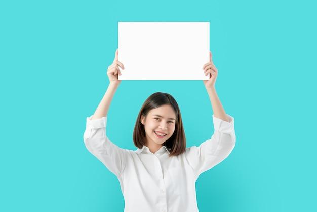 Junge asiatin, die leeres papier mit lächelndem gesicht hält und auf dem blauen hintergrund schaut