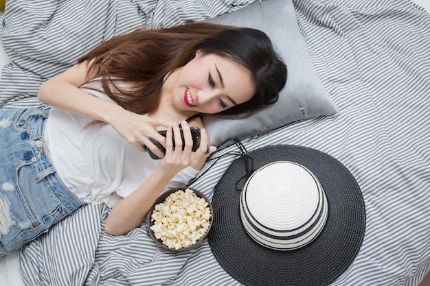 Junge asiatin, die popcorn und note isst oder intelligentes telefon verwendet