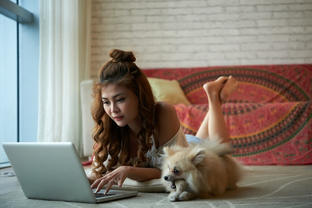 Junge asiatin, die zu hause auf boden mit laptop, mit kleinem schoßhund dazu liegt