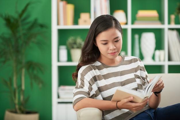 Junge asiatin, die zu hause auf couch und lesebuch sitzt
