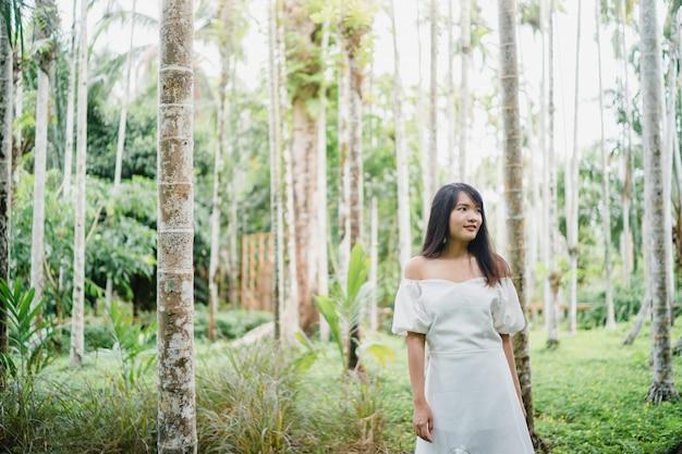 Junge asiatin entspannen sich im wald, die schöne frau, die unter verwendung glücklich ist, entspannen sich zeit in der natur.