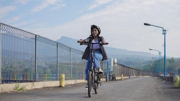 Junge asiatin fährt mit dem fahrrad zur arbeit, sie ist glücklich und sicher