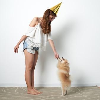 Junge asiatin im spaßpartyhut, der zu hause mit kleinem schoßhund spielt