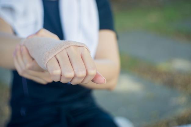 Junge asiatin im trainingsstoff, der hand hält und die handgelenk-schmerz hat