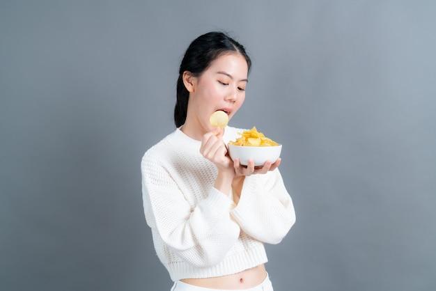 Junge asiatin im weißen pullover isst kartoffelchips