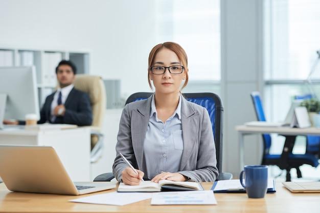 Junge asiatin in den gläsern, die am schreibtisch im büro sitzen, in planer schreiben und kamera betrachten