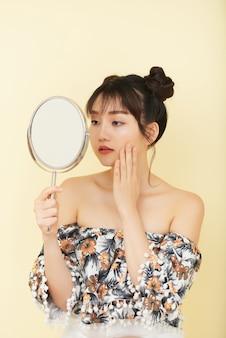 Junge asiatin mit den bloßen schultern, die im studio aufwerfen und in der hand spiegel schauen