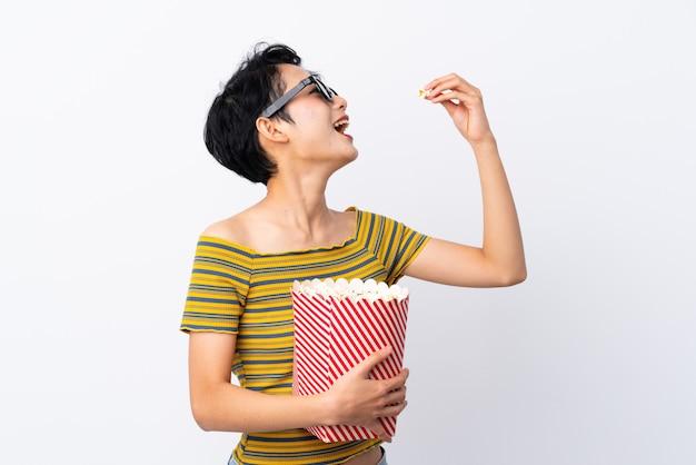 Junge asiatin mit gläsern 3d und halten eines großen eimers popcorns