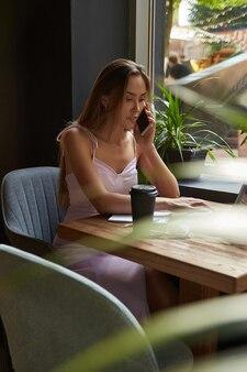 Junge asiatin sitzt im café mit laptop und ruft per smartphone an
