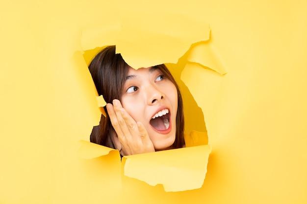 Junge asiatin steckte ihren kopf durch das zerrissene papier