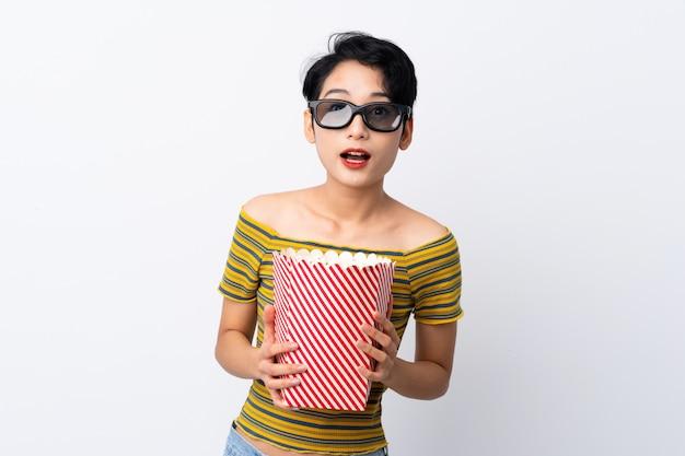 Junge asiatin überrascht mit gläsern 3d und einem großen eimer popcorn halten
