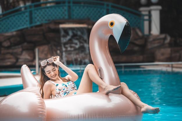 Junge asiatinfahrt auf riesigen aufblasbaren flamingo im swimmingpool.