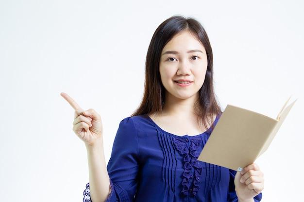 Junge asiatinnen, die ein braunes anmerkungsbuch halten und ihren finger den leeren raum zeigen.
