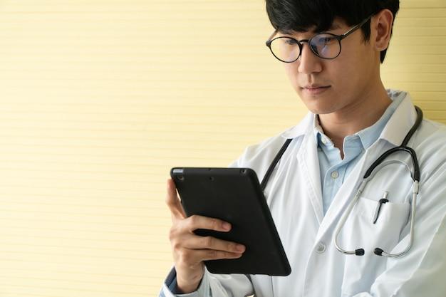 Junge asiatische ärzte verwenden tabletten, um daten und informationen für die gesundheitsuntersuchung von patienten zu überprüfen. konzept von digital, technologie und kommunikation für die medizin.