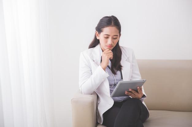 Junge asiatische ärztin, die etwas auf dem tablett-pc liest