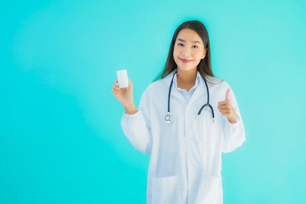 Junge asiatische ärztin mit medizinflasche