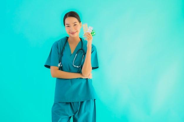 Junge asiatische ärztin mit pille oder droge und medizin