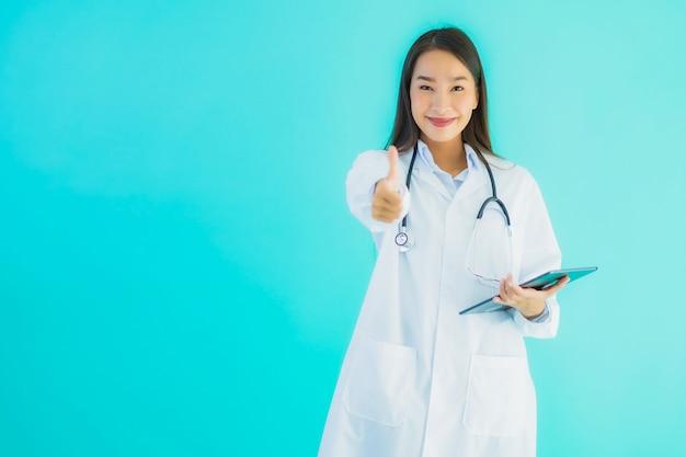 Junge asiatische ärztin mit stethoskop und tablette, die daumen oben zeigt