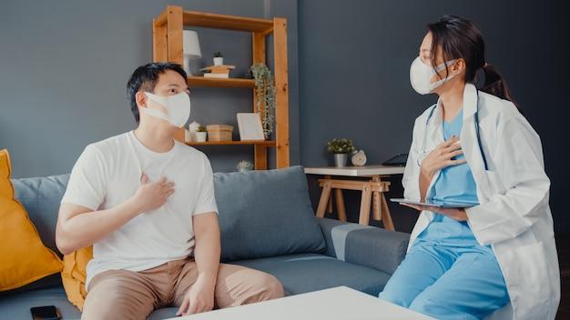 Junge asiatische ärztin tragen gesichtsmaske unter verwendung der digitalen tablette, die gute gesundheitstestnachrichten mit glücklichem männlichem patienten teilt, der auf couch im haus sitzt.