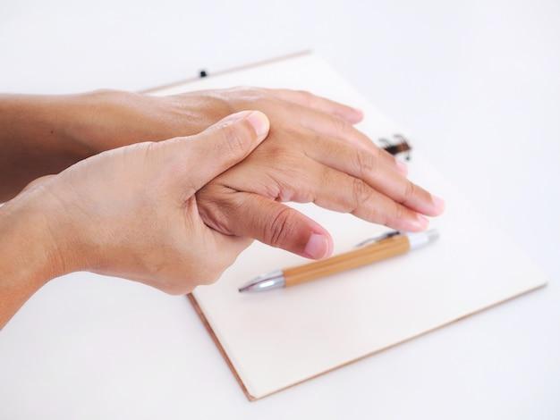 Junge asiatische arbeitende frau, die handschmerzen leidet, finger auslösen und massage auf schmerzhaftem handgelenk. medizinisches symptom und gesundheitskonzept.