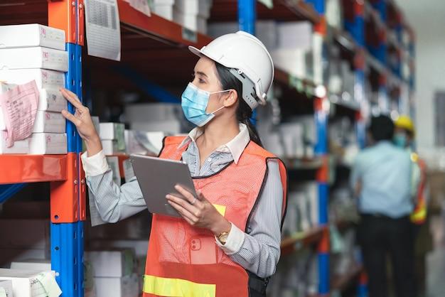 Junge asiatische arbeiterin, die gesichtsmaske mit tablette trägt
