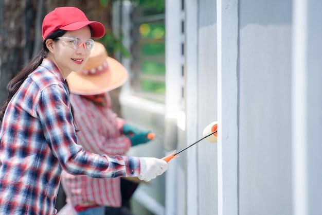 Junge asiatische arbeiterin, die wand des hauses von hand und farbrollerpinsel malt farbe, die grau oder zementfarbe ist