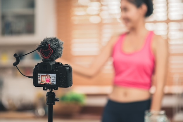 Junge asiatische bloggerfrauenübung und schauen zur kamera in der küche
