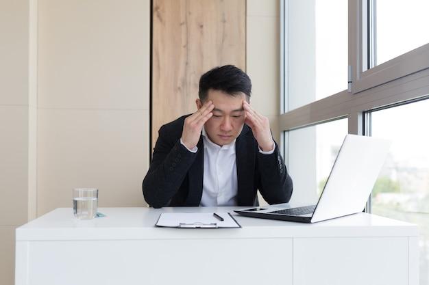 Junge asiatische büroangestellte, die bei der arbeit im büro unter kopfschmerzen leiden, trinkt medizinpille mit wasser. kranker mann im anzug am computer drinnen mit starken schmerzen verwendet das medikament am arbeitsplatz
