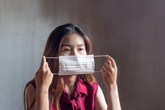 Junge asiatische chinesische thailändische frau, die atemmaske trägt