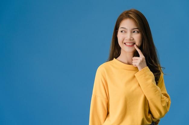 Junge asiatische dame, die lächeln, positiven ausdruck zeigt, gekleidet in lässiger kleidung und spaßgefühl isoliert auf blauem hintergrund. glückliche entzückende frohe frau freut sich über erfolg. gesichtsausdruck konzept.