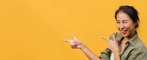 Junge asiatische dame, die mit fröhlichem ausdruck lächelt, zeigt etwas erstaunliches im leeren raum in legerem tuch, das über gelber wand isoliert ist. panoramabanner mit kopienraum.