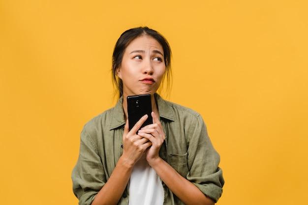 Junge asiatische dame, die telefon mit positivem ausdruck benutzt, breit lächelt, in freizeitkleidung gekleidet ist und sich glücklich fühlt und isoliert auf gelber wand steht. glückliche entzückende frohe frau freut sich über erfolg.