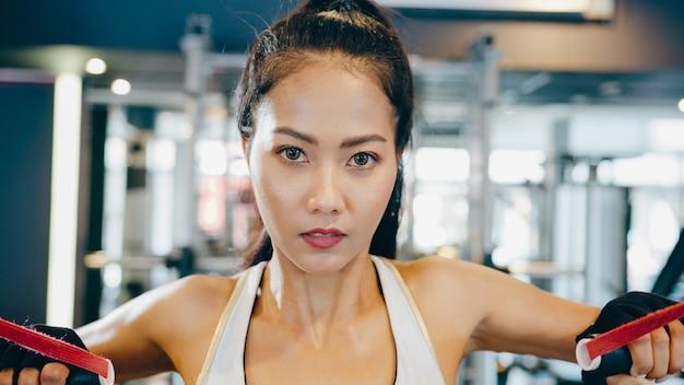 Junge asiatische dame, die übungsmaschinen-kabelkreuzung in der fitnessklasse tut